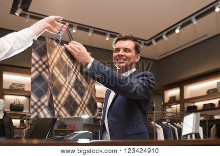 Young businessman with bag in store