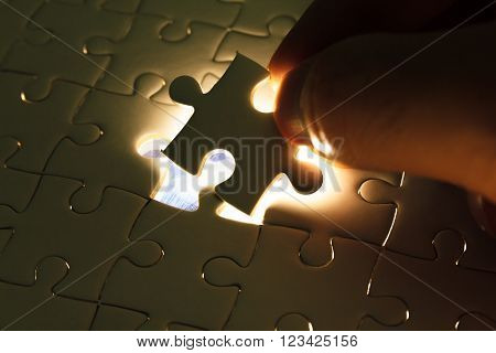 Hand insert missing jigsaw puzzle piece with light glow, business concept for completing the final puzzle piece