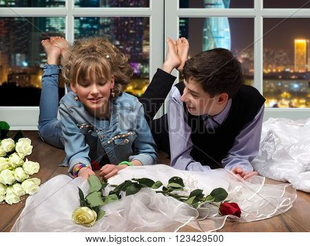 Teenagers lying on the floor, man and woman. Window, night city. Flowers, wedding veil. Love look. The concept of adolescents' attitude, preparation for marriage, love
