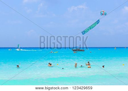 PLAYA DEL CARMEN, MEXICO - JULY 14, 2011: Unidentified people in the water of Caribbean Sea in Mexico. Playa del Carmen area is very popular tourist destination with the most beautiful beaches.