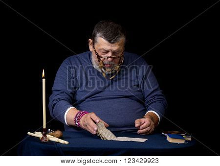 Portrait of an old soothsayer at work table