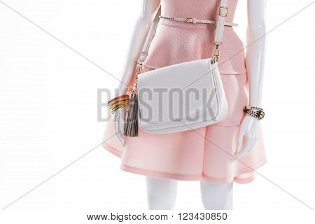 Mannequin with white leather handbag. White purse on female mannequin. Handbag with strap and accessories. Gilded bracelet and white purse.