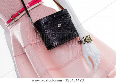 Belts and handbag on mannequin. Female mannequin with classy accessories. Bright belts and dark purse. Vintage purse with dress belts.