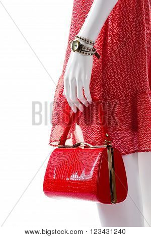 Red purse in mannequin's hand. Female mannequin with glossy handbag. Dotted dress and glossy bag. Bright bag from new collection.