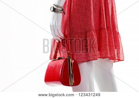 Dress and purse on mannequin. Female mannequin in red clothes. Dotted dress with red bag. Lady's fashionable pieces of clothing.