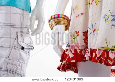 Bracelets and shorts on mannequins. Mannequins in light-colored clothing. Woman's bracelets and men's shorts. Clothes and set of bracelets.