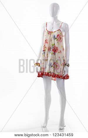 Sarafan and bracelet on mannequin. Female mannequin wearing light clothes. Classic watch and floral sarafan. Seasonal sale of women's clothing.