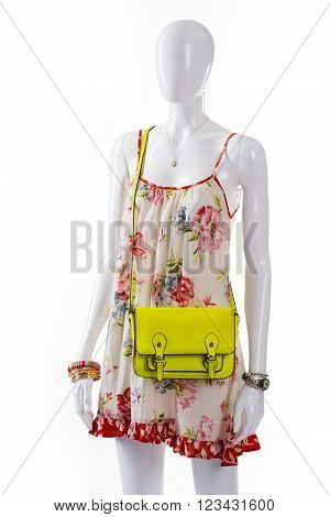 Bag and sarafan on mannequin. Female mannequin wearing lime bag. Lime bag and floral sarafan. Woman's classy light-colored purse.