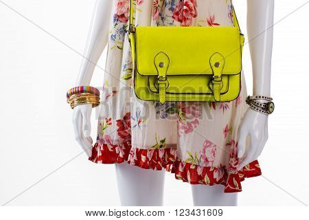 Purse and watch on mannequin. Female mannequin with lime handbag. Casual sarafan with bright bag. Lime purse and golden bracelets.