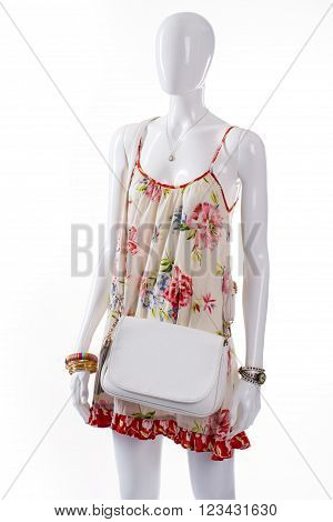 White leather purse on mannequin. Female mannequin wearing simple handbag. Floral sarafan and white bag. Summer clothing with wrist accessories.