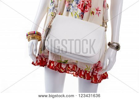 Handbag and accessories on mannequin. Female mannequin wearing wrist accessories. Golden bracelets and white purse. Woman's watch and plain bag.