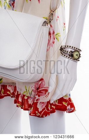 Small wrist watch on mannequin. Female mannequin wearing tiny watch. White leather bag and watch. Woman's accessories sold at discount.