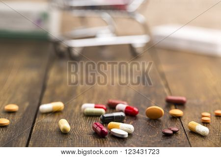 Colorful pillscapsules and pill box on dark wooden background