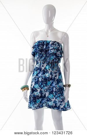 Blue summer dress on mannequin. Female mannequin wearing thin dress. Blue garment with small pendant. Lady's precious accessory and dress.