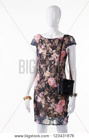 Black vintage purse on mannequin. Female mannequin with retro bag. Floral dress and vintage handbag. Lady's dark classy evening apparel.