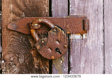 Architectural vintage background - old rusty metal padlock hanging on the wooden textured door. Focus at the padlock. Retro tones processing.