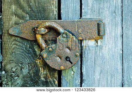Rusty metal padlock at the wooden textured door. Selective focus at the padlock. Vintage tones processing.