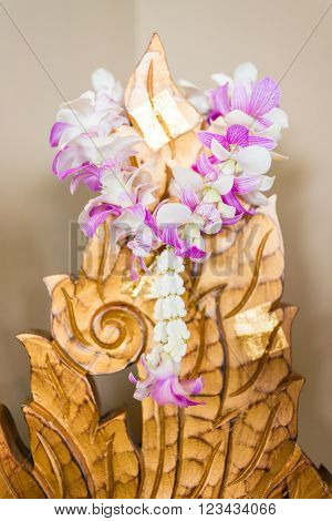garland of orchids flower hang on golden wooden carved with golden leaf decoration. orchid lei.
