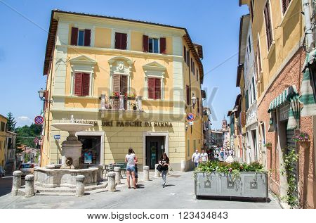 Asciano, Italy, May 31, 2015 - People walk and chat in the small square with fountain