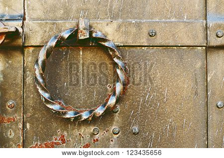 Old grunge metal door with rivets and twisted steel door handle in the form of ring. Vintage tones processing.