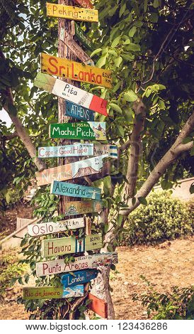 KOS, GREECE - SEPTEMBER 25, 2015: Funny directions signpost with distance to many different countries cities and places