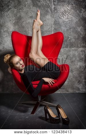 Beautiful blonde girl in a black slinky dress  lies in the red chair. The woman took off her shoes and resting lifted up foot rests