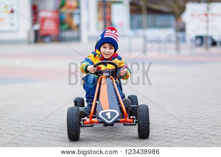 Funny little preschool kid boy having fun with toy race car, outdoors. Child driving car. Outdoor games for children concept. On spring or autumn day.