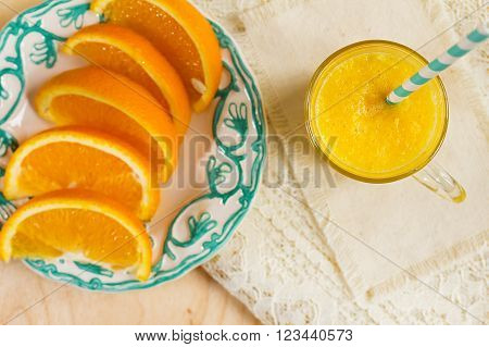 Fresh orange juice. Orange smoothies and sliced orange on the plate. Fresh orange smoothie downward view on slate. Focus on the glass of juice.