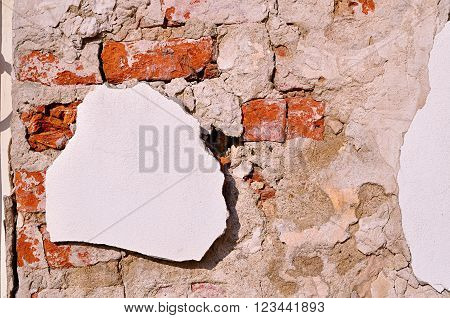 Old red brick wall with white pieces of old stucco. Vintage architectural background
