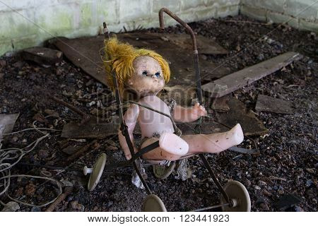 Old abandoned doll on a broken toy stroller at the abandoned house
