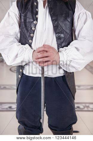 Handsome man in medieval clothes holding dagger