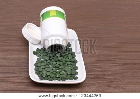 Spirulina super food tablets flowing out of plastic container