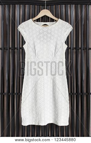 White lacy dress on clothes rack hanging on black rattan screen