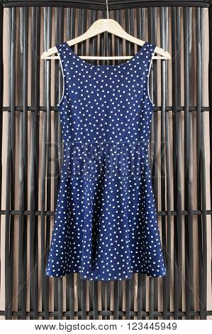 Blue sundress on clothes rack handing on black bamboo screen