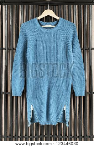 Blue knitted dress on clothes rack hanging on black bamboo screen