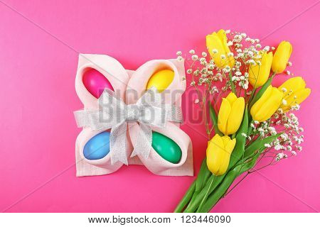 Multicoloured Easter eggs and tulips on pink background