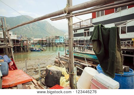 HONG KONG, CHINA - FEBRUARY 11, 2016: Rusty metal buildings of fishermen with riverboats of fishing village Tai O on February 11, 2016. Hong Kong dollar is the eighth most traded currency in the world.
