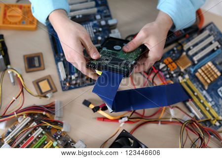 Young man repairing computer hardware in service center