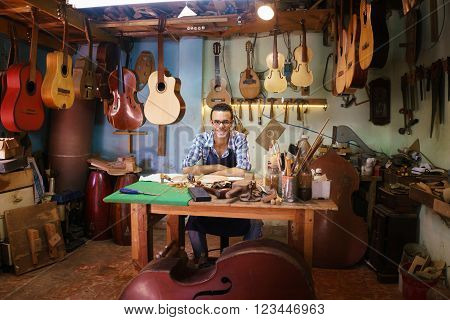 Portrait Of Happy Artisan Lute Maker In Guitar Shop Smiling