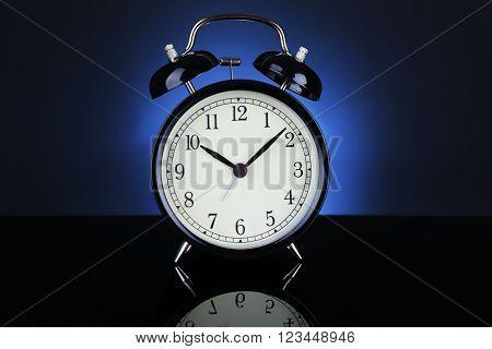 Alarm clock on a dark blue background.