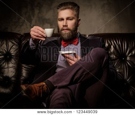 Old-fashioned bearded man sitting in comfortable leather sofa with cup of coffee isolated on gray.