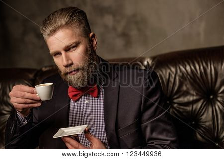 Old-fashioned bearded man sitting in comfortable leather sofa with cup of coffee
