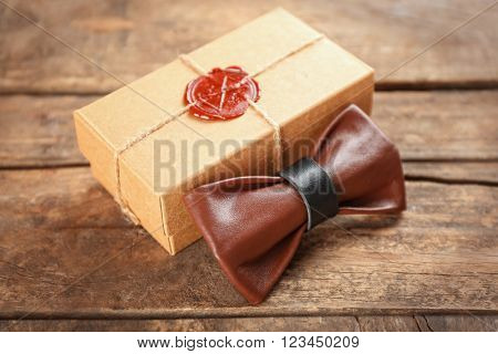 Brown and black leather bow tie and cardboard gift box with red seal on wooden table, close up