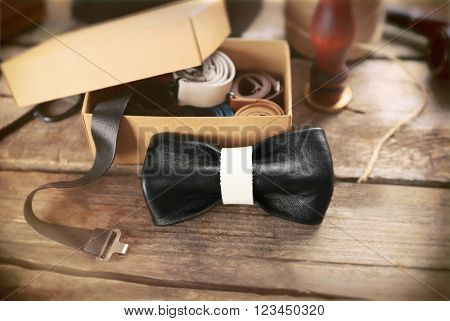 Black and white bow tie and full cardboard gift box of ties on wooden table, close up