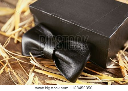Black leather bow tie with special packaging on a thatch, close up