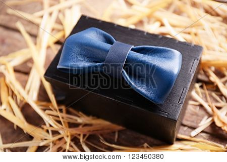 Blue leather bow tie with special packaging on a thatch, close up