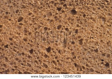 Brown bread, background texture, detailed look at the rye porous brown bread slice, macro view