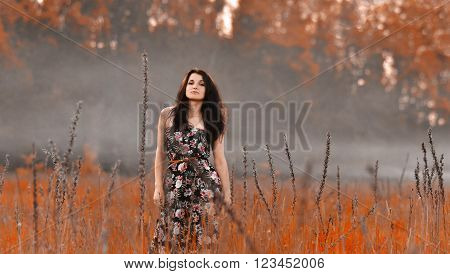 Very beautiful, attractive, slim, nice, cool, pretty girl in the red, yellow field with gray, heavy fog. Nature with amazing view. Nice girl with field with fog. Red sunset, Magic, fantasy view. Pretty girl in fog
