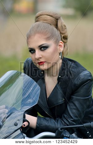 Portrait of glamour, fashionable, beautiful, attractive, snorting, stunning, nice, pretty biker girl sitting on the black, new, modern motorbike, motorcycle, biker girl with smokey  eyes, professional hairstyle.