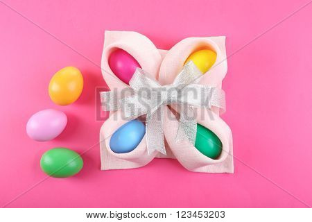 Multicoloured Easter eggs wrapped in napkin with bow on pink background